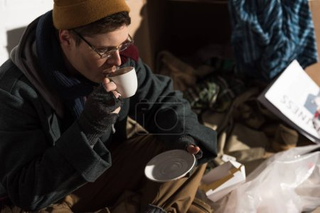 Photo for Homeless man in glasses and fingerless gloves drinking coffee - Royalty Free Image