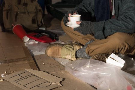 Photo for Cropped view of homeless man holding coffee cup while sitting surrounded by rubbish - Royalty Free Image