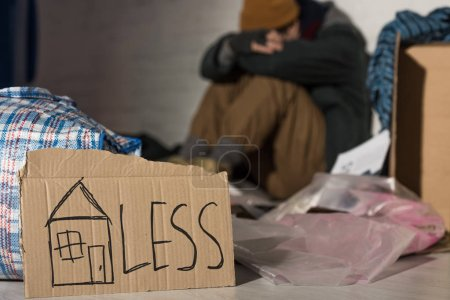 """Photo for Selective focus of homeless man holding head on knees while sitting on rubbish dump with cardboard card """"homeless"""" lettering - Royalty Free Image"""
