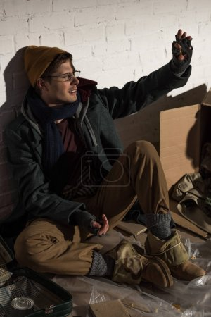 Photo for Homeless beggar man sitting by brick wall and waving hand - Royalty Free Image