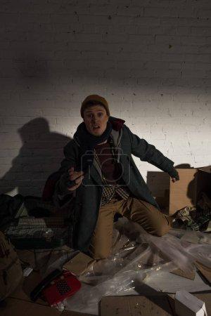 Foto de Borracho vagabundo enojado sobre rodillas en vertedero - Imagen libre de derechos