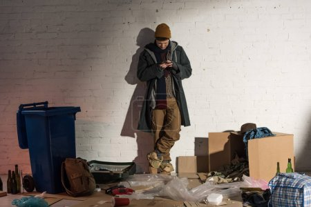 Photo for Homeless man using smartphone while standing by white brick wall surrounded by rubbish - Royalty Free Image