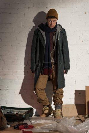sad homeless man standing by white brick wall and looking at camera