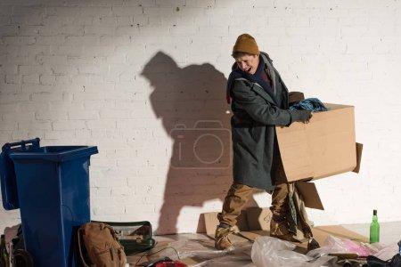 Photo pour Sans-abri en colère tenant boîte en carton avec poubelle - image libre de droit