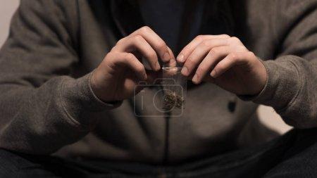 Photo pour Foyer sélectif de junkie homme ouverture pack avec marijuana - image libre de droit