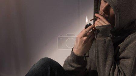 Photo pour Toxicomane homme dans capuche éclaircissant roulé cigarette de marijuana - image libre de droit