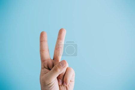 Photo for Cropped view of fingers showing peace symbol isolated on blue - Royalty Free Image