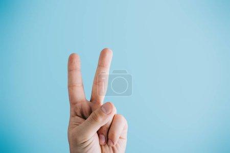 Foto de Vista recortada de dedos que muestra el símbolo de la paz aislado en azul - Imagen libre de derechos