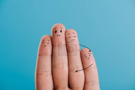 cropped view of upset fingers family isolated on blue