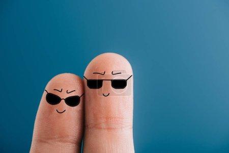 Photo pour Vue recadrée des doigts souriants dans les lunettes de soleil isolées sur bleu - image libre de droit
