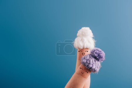 Photo pour Vue recadrée de doigts comme des amis heureux en chapeaux tricotés isolé sur bleu - image libre de droit