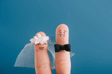 Photo for Cropped view of fingers as happy bride and nervous groom isolated on blue - Royalty Free Image