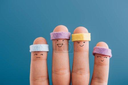 Photo pour Vue recadrée des doigts sportifs heureux dans les bandeaux isolés sur bleu - image libre de droit
