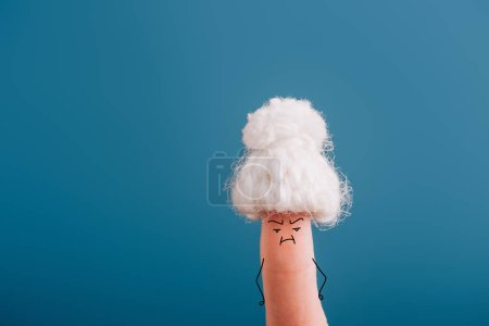 Photo pour Vue recadrée de doigt comme vieille femme en bonnet tricoté avec mauvaise humeur isolé sur bleu - image libre de droit