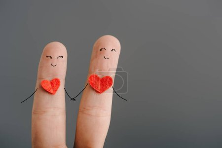 Photo for Cropped view of happy couple of fingers with hearts holding hands isolated on grey, valentines day concept - Royalty Free Image