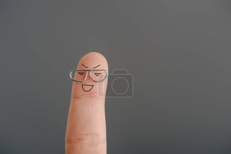cropped view of one joyful finger in eyeglasses isolated on grey