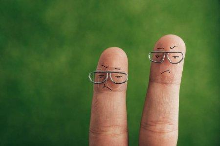 Photo pour Vue recadrée des doigts frustrés de mauvaise humeur sur vert - image libre de droit