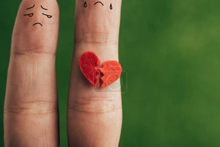Photo for Cropped view of fingers as sad couple with broken heart  on green - Royalty Free Image