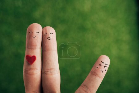 cropped view of fingers as happy couple and jealous person on green