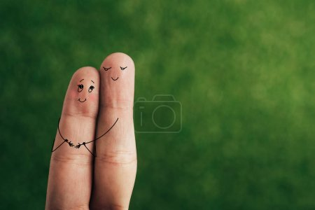 cropped view of happy couple of fingers hugging on green