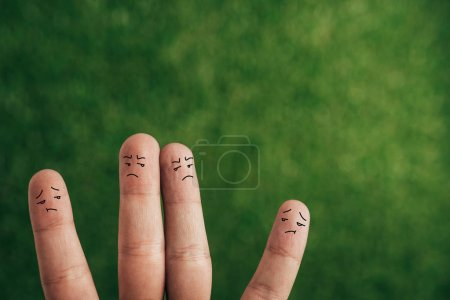 Photo for Partial view of dissatisfied fingers in bad mood on green - Royalty Free Image