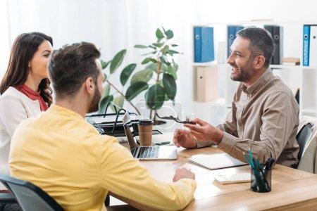 Photo pour Conseiller assis à table et portable avec homme et femme dans le bureau - image libre de droit