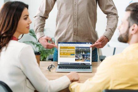 Photo pour Mise au point sélective de conseiller avec doigts à ordinateur portable avec le site de réservation sur l'écran de pointage pour homme et femme dans le bureau - image libre de droit