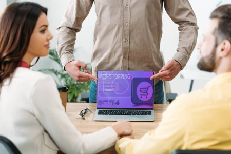 Photo for Selective focus of advisor pointing with fingers at laptop with web shopping website on screen to couple in office - Royalty Free Image