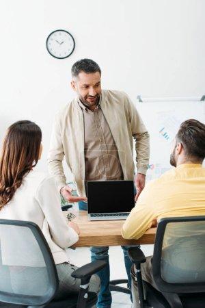 Photo pour Conseiller en pointant avec main à ordinateur portable avec écran blanc aux investisseurs au bureau - image libre de droit