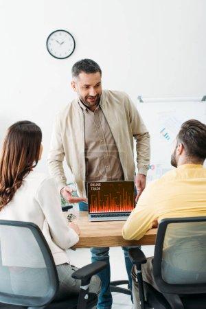Photo pour Conseiller en pointant avec main à ordinateur portable avec le site Web de commerce en ligne à l'écran pour les investisseurs dans le bureau - image libre de droit