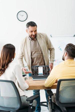 Photo pour Conseiller en pointant avec la main pour ordinateur portable avec linkedin site Web sur l'écran aux investisseurs au bureau - image libre de droit