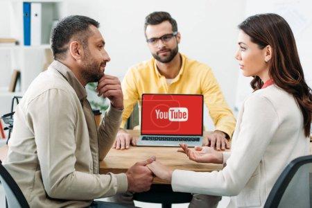 Photo pour Mise au point sélective d'homme et femme tenant par la main près de conseiller et portable avec youtube site sur écran au bureau - image libre de droit