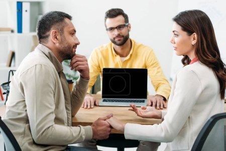 Photo pour Mise au point sélective d'homme et femme tenant par la main à table avec le conseiller et l'ordinateur portable avec écran blanc au bureau - image libre de droit