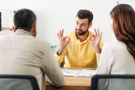 Photo pour Mise au point sélective du conseiller assis à table et montrant okey signe pour homme et femme dans le bureau - image libre de droit