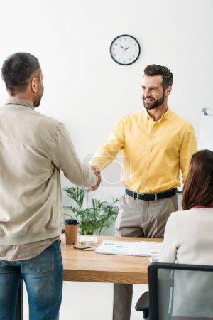 Photo pour Conseiller et investisseur se serrant la main au-dessus de table wile femme assise au bureau - image libre de droit