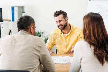 Photo pour Mise au point sélective du conseiller assis à table et souriant aux investisseurs au bureau - image libre de droit