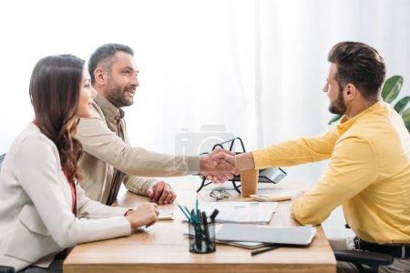 Photo pour Femme assise à table wile conseiller et investisseur se serrant la main au-dessus de la table au bureau - image libre de droit