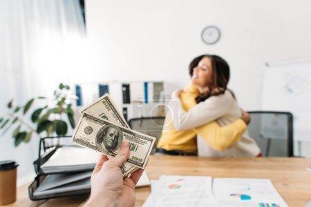 Photo pour Mise au point sélective du conseiller à la table contenant les billets de dollar wile investisseurs étreindre au bureau - image libre de droit