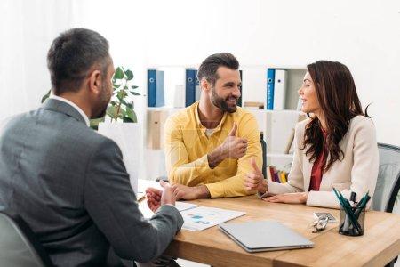 Photo pour Investisseurs, assis à table et feuilletant ups près de conseiller au bureau - image libre de droit