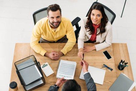 Photo pour Vue grand angle du conseiller donnant le contrat aux investisseurs à table dans le bureau - image libre de droit