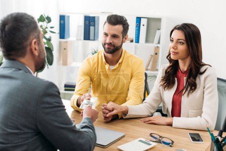 Photo pour Investisseurs de couple assis à table et prendre dollar billets de conseiller au bureau - image libre de droit
