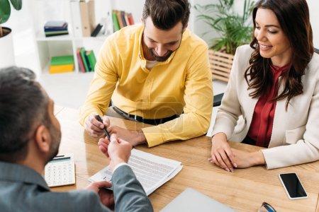 Photo pour Conseiller assis à table et donnant la plume et le document aux investisseurs en fonction - image libre de droit
