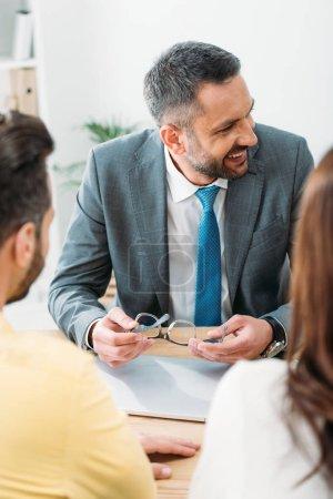 Photo pour Conseiller en souriant, assis à table et tenant des lunettes avec des investisseurs au bureau - image libre de droit