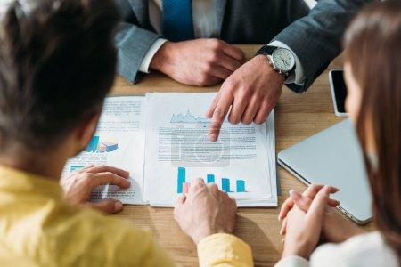 Photo pour Recadrée vue d'investisseurs assis à table et main dans la main bien que conseiller en pointant avec le doigt les documents au bureau - image libre de droit