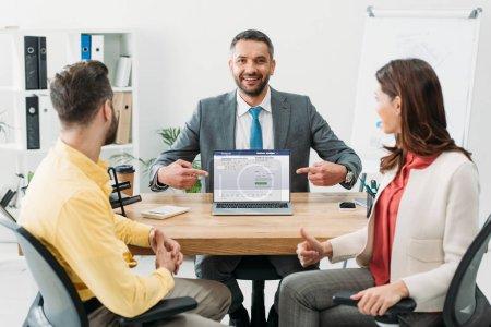 Photo pour Conseiller en pointant avec doigts à ordinateur portable avec facebook site Web sur l'écran tandis que l'homme et la femme pied vers le haut au bureau - image libre de droit