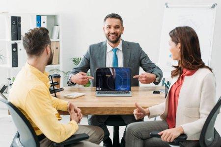 Photo pour Conseiller en pointant avec doigts à ordinateur portable avec le site de réservation sur l'écran près de l'homme et femme pied vers le haut dans le bureau - image libre de droit