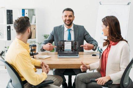 Photo pour Conseiller en pointant avec doigts à ordinateur portable avec le site linkedin sur écran près de l'homme et femme pied vers le haut dans le bureau - image libre de droit