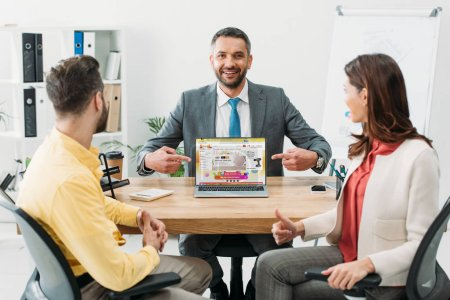 Photo for Advisor pointing with fingers at laptop with aliexpress website on screen near man and woman thumbing up in office - Royalty Free Image