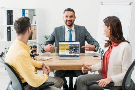 Photo pour Conseiller en pointant avec doigts à ordinateur portable avec le site Web de réservations sur écran près d'investisseurs au bureau - image libre de droit