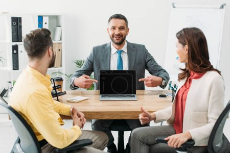 Photo pour Conseiller en pointant avec doigts à ordinateur portable avec écran blanc près de homme et femme à pied vers le haut au bureau - image libre de droit
